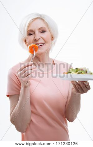 Enjoy your meal. Happy aged female keeping her eyes closed while eating tomato holding plate with salad in left hand, isolated on white background