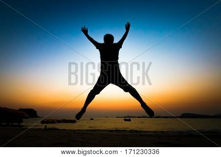 Back view of unidentified silhouette young man jumping over the sea beach with sunset background