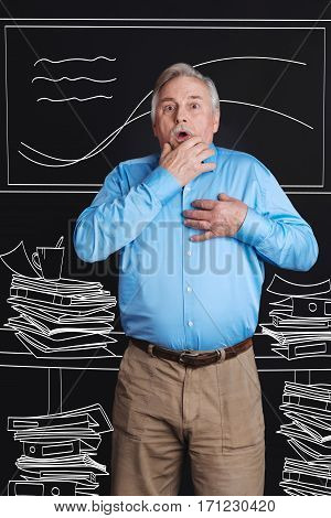 Heavy workload. Nice aging stressed man standing among piles of paper and holding his hand near his heard while working at the office