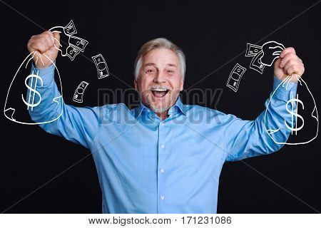 Winning the lottery. Delighted positive elderly man standing against the black background and holding bags with money while being happy