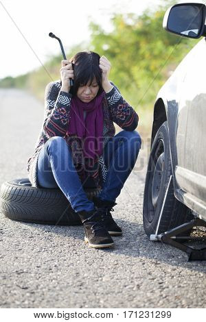 Woman changing a wheel on a car on the empty road Selective focus and small depth of field