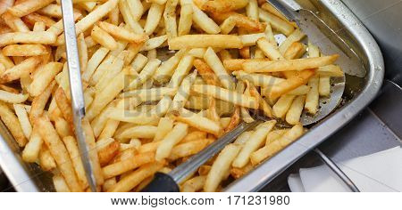 French fries fresh cooked. Restaurant deep fryer, metal container with lots of potatoes fried. Street food, fast food. Potato fries closeup. Roasted tasty potatoes