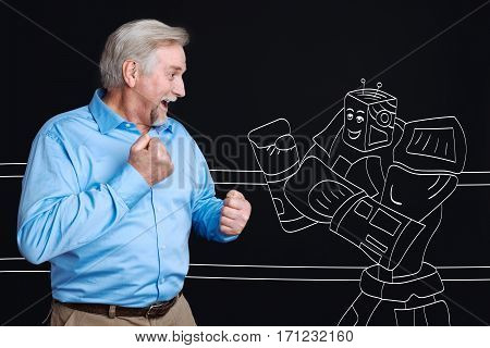 Age of technology. Positive joyful aged man holding fists and standing apposite the robot while having a fight with him