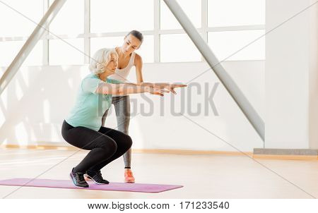 Physical exercises. Beautiful female fitness couch standing near the woman and looking at her while having a workout