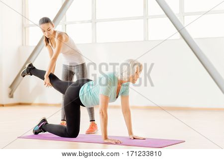 Intensive training. Pleasant nice senior woman holding her leg up and looking forwards while exercising on a yoga mat