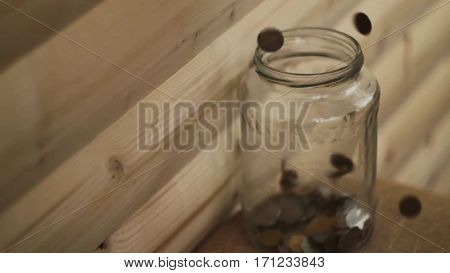 pennies droped into a transparent jar on wooden background.