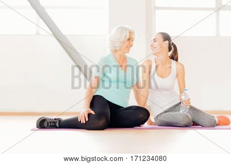 Having a break. Cheerful delighted positive women sitting on a yoga mat and looking at each other while having a break from the workout