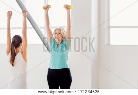 Build up your body. Joyful active aged woman standing and lifting small rubber dumbbells while repeating the exercise after her fitness coach