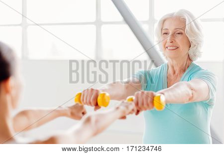 Enjoying the exercise. Pleasant happy grey haired woman smiling and holding small rubber dumbbells in front of her while enjoying her fitness training