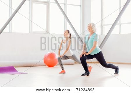 Let us do it together. Pleasant good looking well built women standing near each other and doing physical exercises while enjoying their fitness class