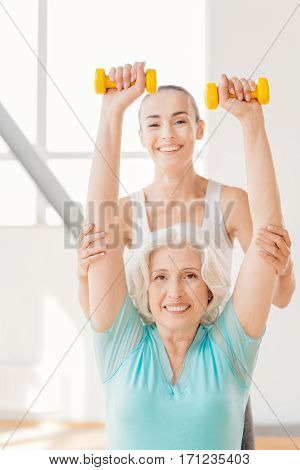 Pleasant workout. Happy delighted senior woman looking at you and smiling while lifting small rubber dumbbells
