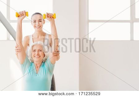 Fitness class. Positive delighted young coach standing behind the elderly woman and smiling while helping her to lift dumbbells