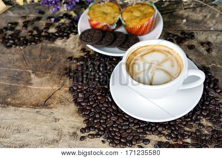 Cappuccino coffee and chocolate cookies. A cup of latte, cappuccino or espresso coffee with milk put on a wood table with dark roasting coffee beans. Drawing the foam milk on top.