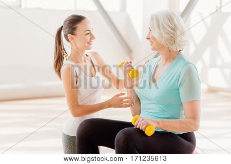 Developing muscles. Cheerful nice senior woman smiling and looking at her fitness coach while training with dumbbells