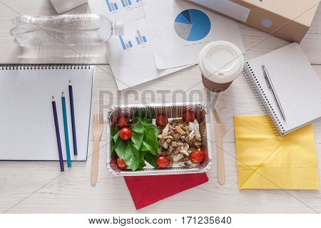 Healthy business lunch in the office, coffee take away cup and vegetables with chiken and mushrooms in foil container, top view on white wooden desk. Snack at break time