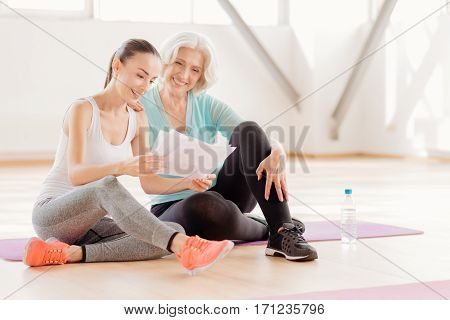 Scheme for fitness training. Joyful delighted positive women sitting together and reading the workout plan while preparing for fitness training