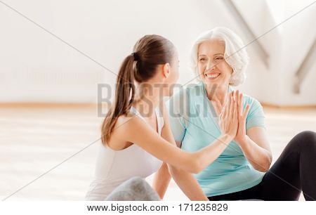 Wonderful mood. Happy nice pleasant women looking at each other and giving high five while working out together in the gym
