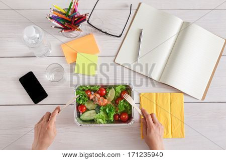 Healthy business lunch in the office, top view of eating person. Salad plate with salmon on white wooden desk near mobile phone and open organizer. Snack at break time
