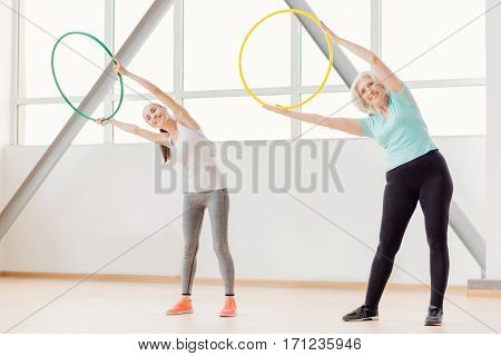 Fitness equipment. Good looking delighted sporty women holding hula hoops and doing bending exercises while having a fitness workout