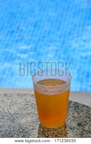 Lager in plastic glass by poolside on table