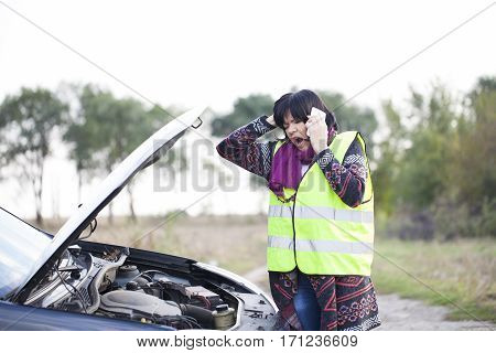 Woman call for help because of a malfunction the car on the road Selective focus and small depth of field