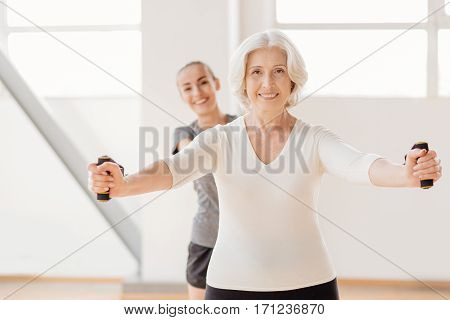 Involved in the workout. Hard working pleasant elderly woman standing in front of her coach and exercising with a resistance band while having fitness classes