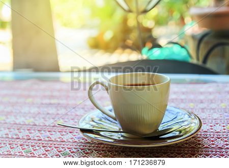 Cup of coffee on the table in coffee shop with morning sunlight and copy space for any design
