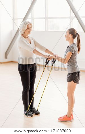 Resistance band training. Positive active elderly woman standing opposite her fitness coach and exercising with a resistance rubber band while having a workout
