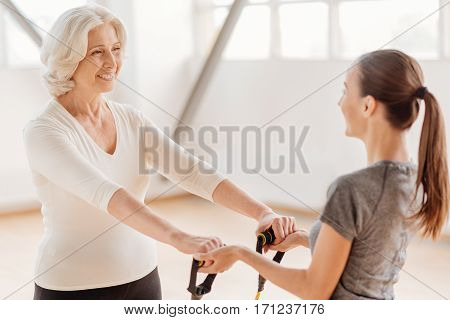 I like fitness. Happy delighted aged woman looking at her coach and smiling while exercising with a rubber band