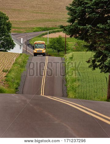school bus driving on a hilly, country road