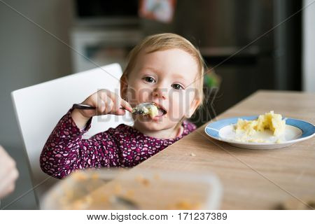 Cute little girl sitting at the kitchen table eating mashed potatoes