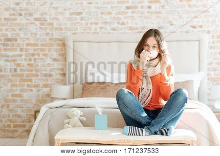 Suffering from flu. Depressed disappointed young woman sitting on the bed at home and suffering from influenza while holding hanky and touching her nose
