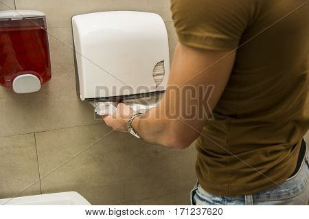 Back view of hands of person taking the paper towels.