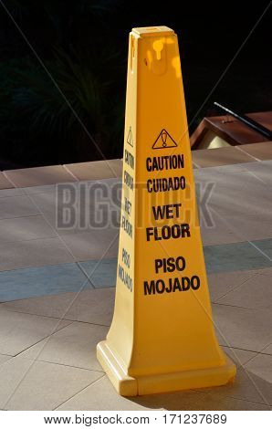 Yellow wet floor warning cone on floor