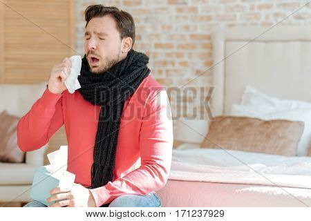 Sneezing all day. Ill bearded young man sitting on the bed at home and suffering from influenza while holding hanky and sneezing