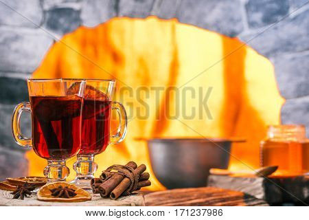Mulled wine in irish glasses. Pan next to hearth frame on the background