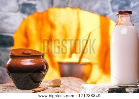 Clay pot and milk bottle on the serving boards in front of oven hearth with boiling pan