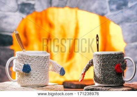 Tea mugs in sweater cozies with teaspoons inside. Fireplace frame on the background