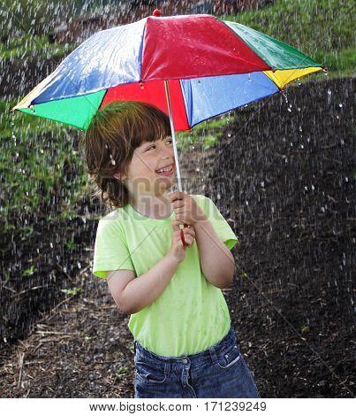 Laughing boy under an umbrella outdoor in rain
