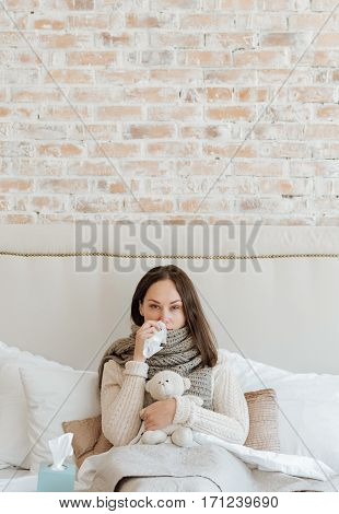 Feeling tired . Upset depressed young woman sitting on the bed at home and suffering from influenza while holding handkerchief and touching her nose