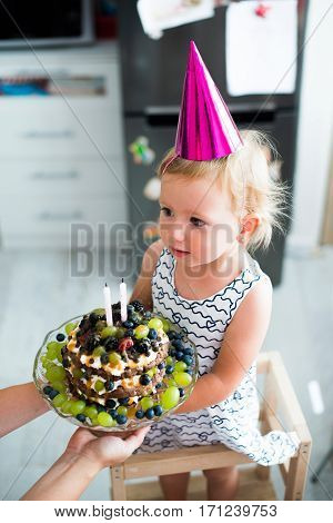 Unrecognizable young mother giving her daughter fruit birthday cake with two candles. Pink party hat on head.