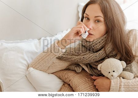 Tired from being sick. Upset exhausted young woman lying in the bed at home and suffering from influenza while holding handkerchief and hugging the fluffy toy