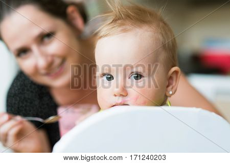 Beautiful young mother feeding her baby daughter with fruit yogurt