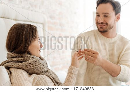 Effective nasal drops. Smiling bearded helpful man sitting on the bed at home and holding nasal drops while expressing love and taking care about his girlfriend