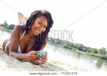 young woman at the beach holding her mobile phone