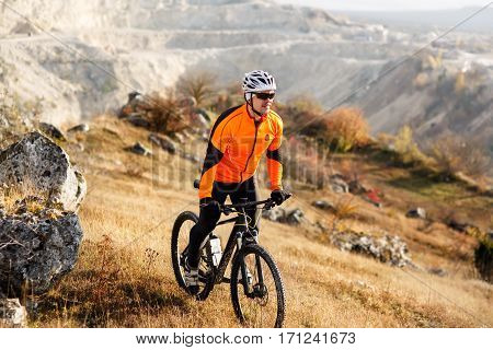 Cyclist in Red Jacket Riding the Bike Down Rocky Hill. Extreme Sport Concept. Space for Text. Cycler in the helmet and glasses. Travel in the countryside. Spring season.