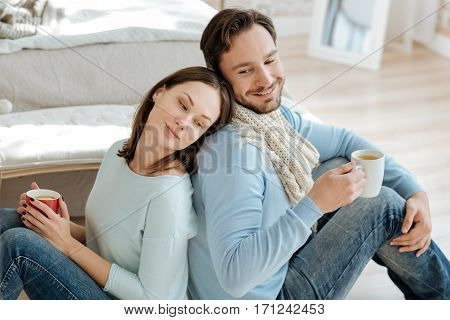 Overcoming coldness together. Happy smiling charismatic couple sitting in the bedroom back to back while expressing care and drinking hot tea with lemon