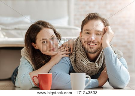 Delighted from being together. Positive smiling young couple lying on the floor at home while expressing harmony and drinking hot tea