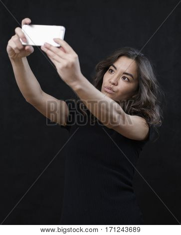asian girl taking selfie snapshot  on dark background
