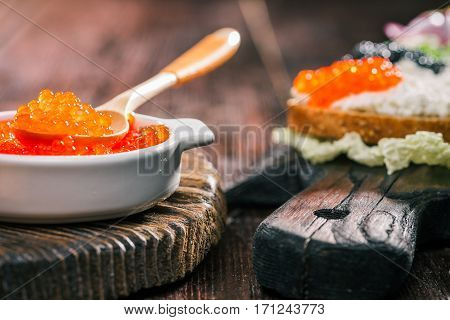 Salmon roe and sandwiches with farmer cheese on wood boards